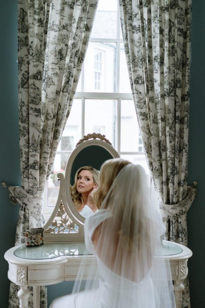 Bride putting on earrings in mirror at Castle Leslie wedding