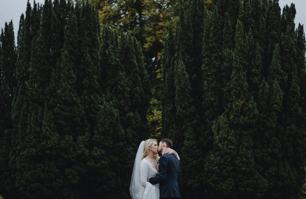 bride and groom kissing in the gardens of Castle Leslie