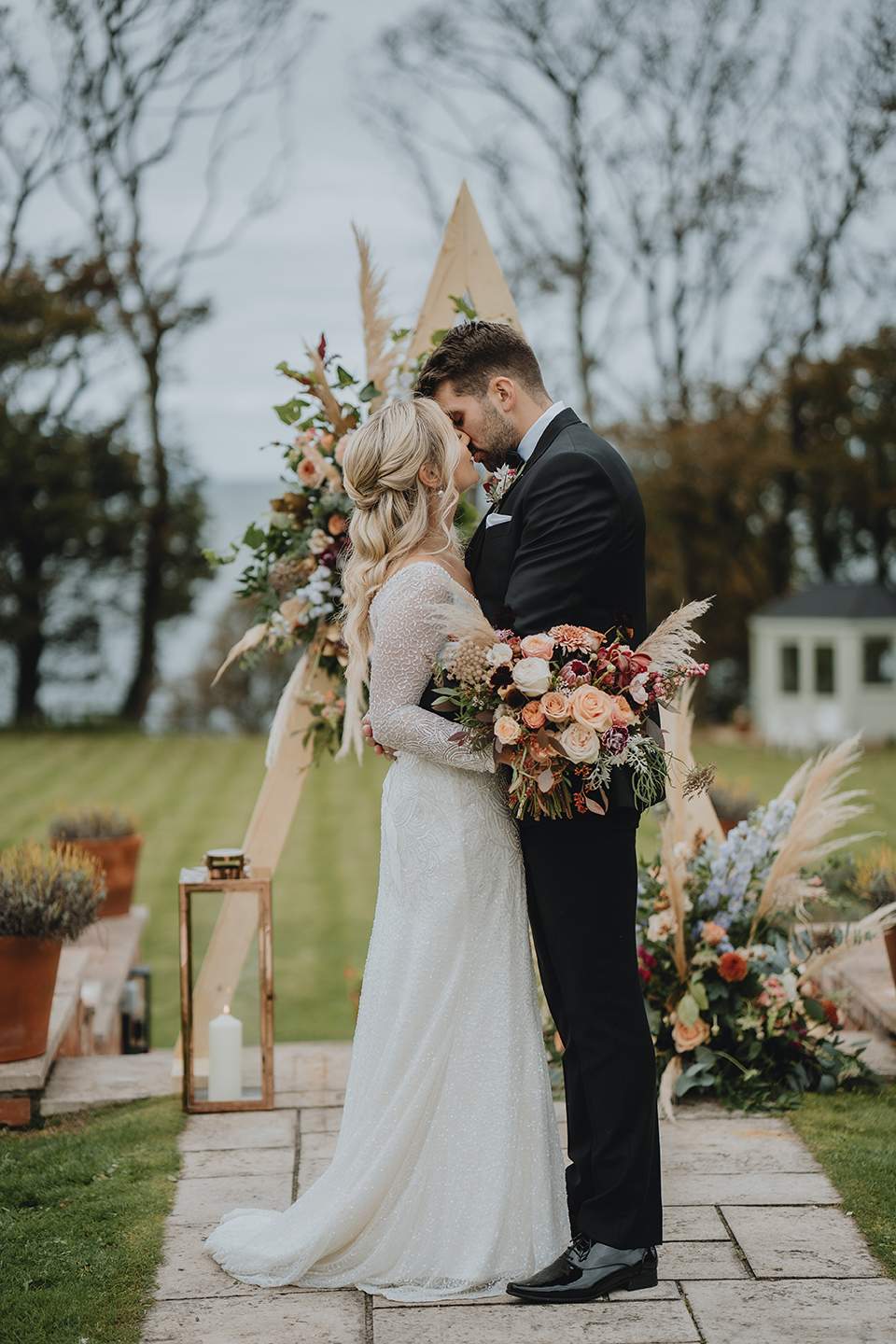 bride and groom kissing at the end of their outdoor ceremony in the grounds of Hillmount House. They have a triangular floral arch behind them.