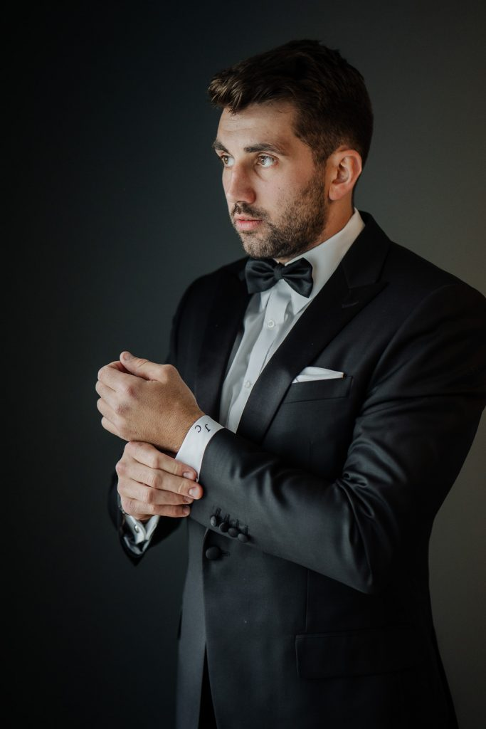 groom in black tuxedo and bow tie