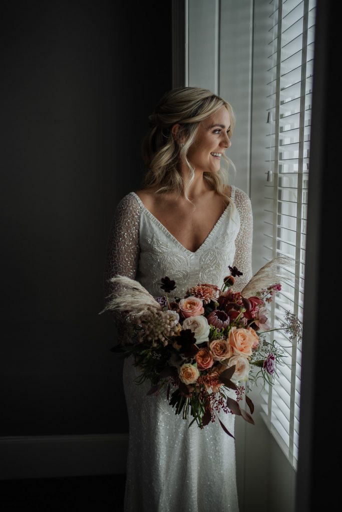 bride at window with large floral bouquet