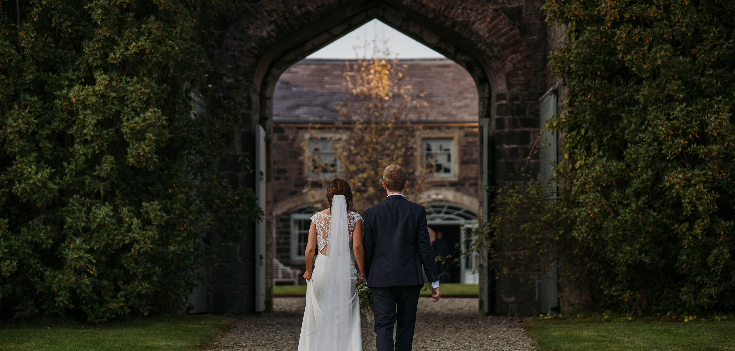 bride and groom walking through large castle archway